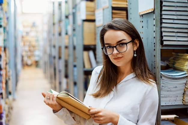 Schönes mädchen mit altem buch in der bibliothek