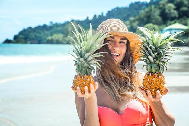 Schönes mädchen mit ananas an einem exotischen strand, eine fröhliche stimmung und ein schönes lächeln, nahaufnahme