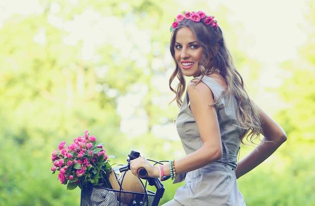 Schönes mädchen mit blumen auf einem fahrrad