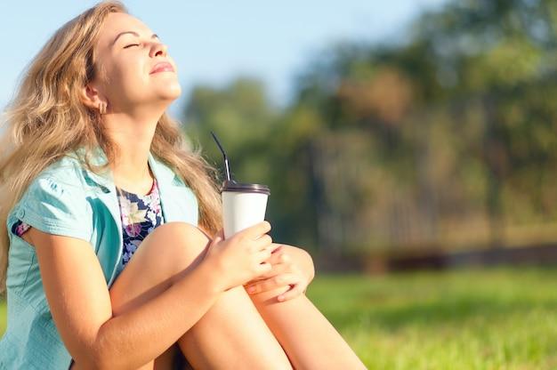 Schönes mädchen mit cup in der hand den sonnenuntergang genießend.