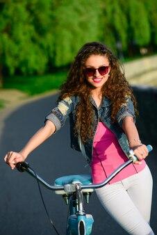 Schönes mädchen mit dem gelockten haar, das sonnenbrille trägt, die auf einem fahrrad im park im sommer in der stadt reitet