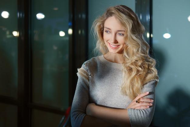 Schönes mädchen mit dem langen gelockten blonden haar, das mit den gekreuzten händen aufwirft. natürliches make-up und perfekte haut.