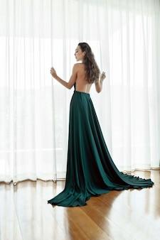 Schönes mädchen mit dem langen gelockten haar, das in einem schönen abendkleid mit einem offenen rücken aufwirft.
