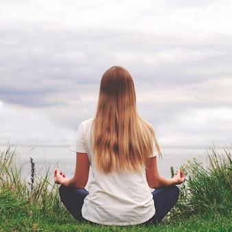 Schönes mädchen mit dem langen haar, das auf dem ufer sitzt. blick von hinten. sonnenuntergang. yoga am see