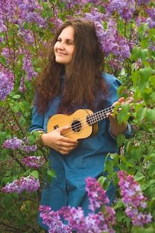 Schönes mädchen mit dem lockigen haar kleidete im denimkleid an, welches die ukulele spielt