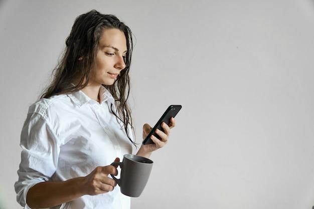Schönes mädchen mit dem nassen haar und schale coffe, die auf smartphone simsen. exemplar morgenroutine