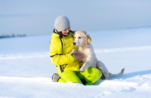Schönes mädchen mit dem schönen hund draußen im winter