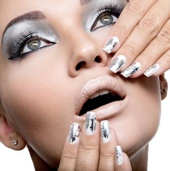Schönes mädchen mit dem silbernen make-up und den metallnägeln.