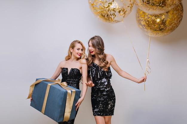 Schönes mädchen mit den blonden haaren, die mit vergnügen nach der geburtstagsfeier aufwerfen. ekstatisches kaukasisches weibliches modell mit lockiger frisur, die mit leuchtenden luftballons steht und freund ansieht.