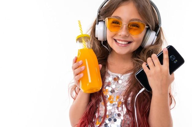 Schönes mädchen mit den großen weißen kopfhörern, die schwarzen smartphone und flasche mit orangensaft halten