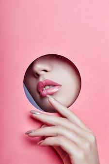 Schönes mädchen mit den rosa prallen lippen späht loch