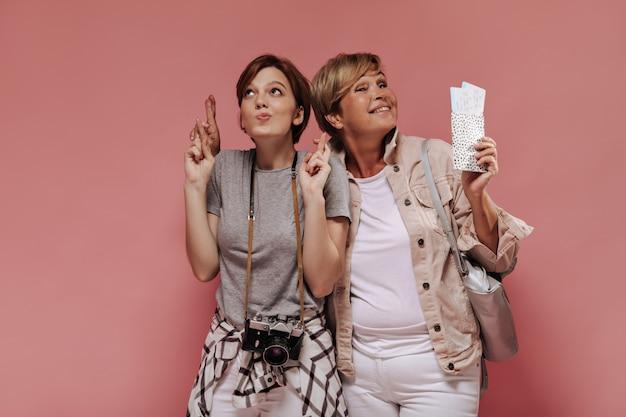 Schönes mädchen mit dunklem haar in grauem t-shirt und kariertem hemd, das ihren finger kreuzt und mit blonder frau mit eintrittskarten auf rosa hintergrund aufwirft.