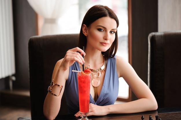 Schönes mädchen mit einem cocktail im café.