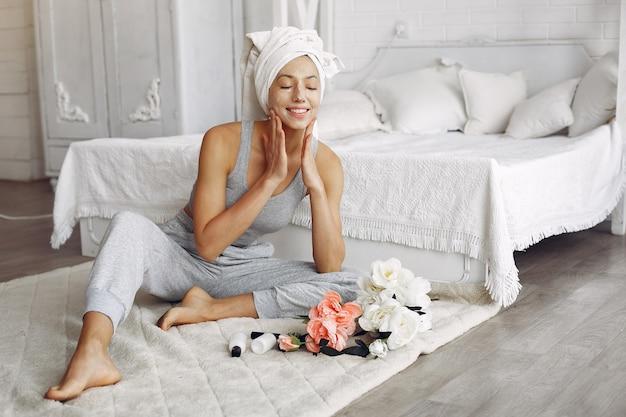 Schönes mädchen mit einem handtuch unter verwendung eines schönheitsprodukts