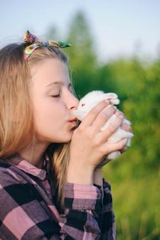 Schönes mädchen mit einem kaninchen. mädchen lacht und küsst ein kaninchen. kartenhemd und jeans. osterhase.