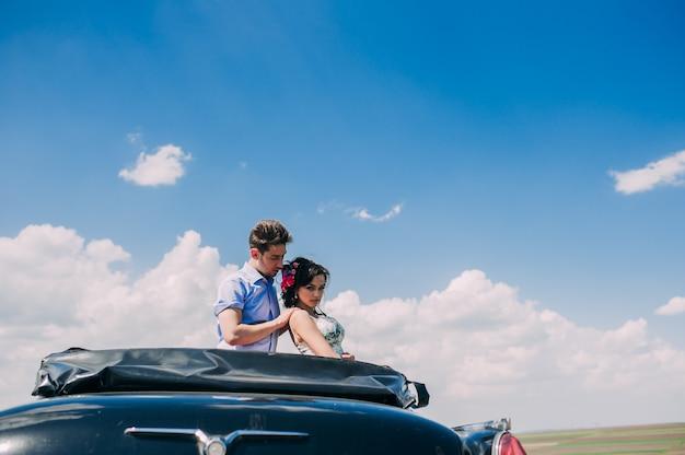 Schönes mädchen mit einem kerl in einem retro- auto