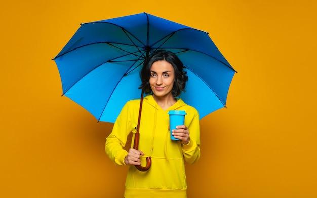Schönes mädchen mit einem lächeln im gesicht unter einem blauen regenschirm, gekleidet in einen gelben kapuzenpulli, den blauen thermobecher in der linken hand haltend, bereit für den regnerischen tag.