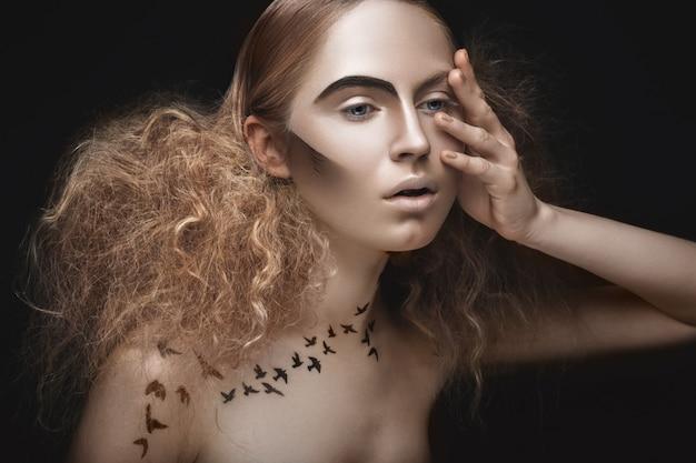 Schönes mädchen mit einem muster auf dem körper in form von vögeln, kreativem make-up und frisur üppig.