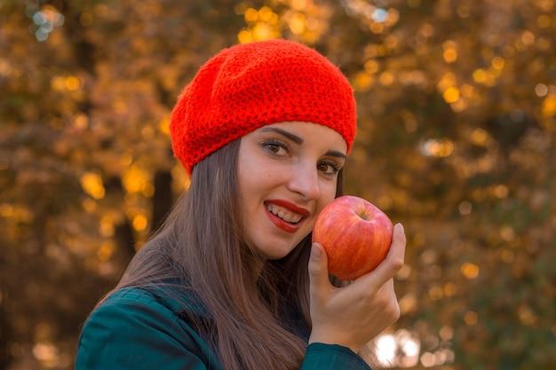 Schönes mädchen mit einem roten hut, das auf der straße steht, lächelt und hält apple in der hand nahaufnahme