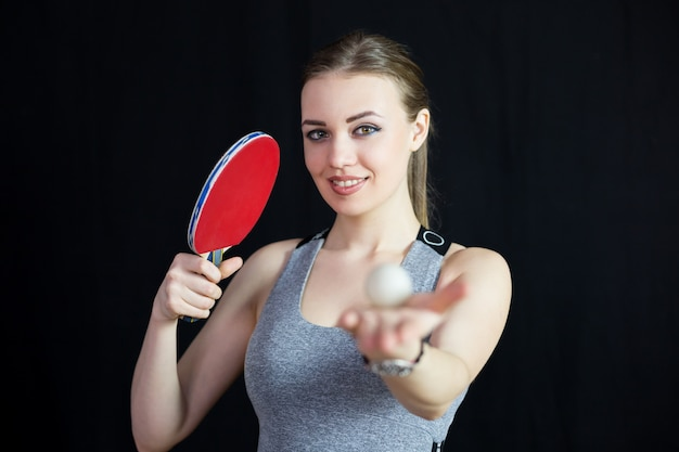 Schönes mädchen mit einem tennisschläger und einer kugel.
