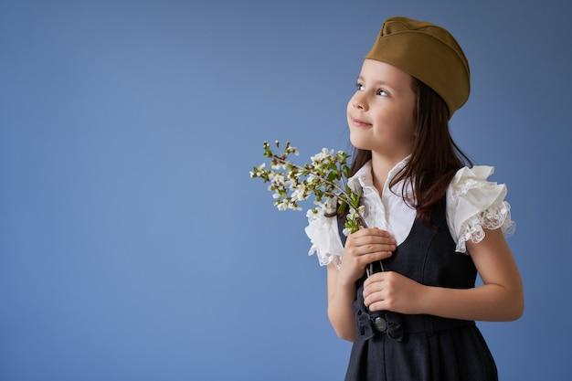 Schönes mädchen mit einem zweig eines blühenden baumes zum thema des 9. mai, siegtag