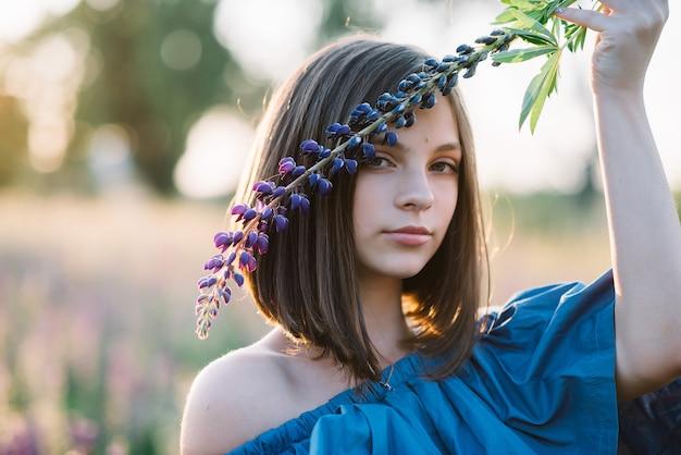 Schönes mädchen mit einer lupinenblume in ihren händen in einem feld bei sonnenuntergang. nahansicht.