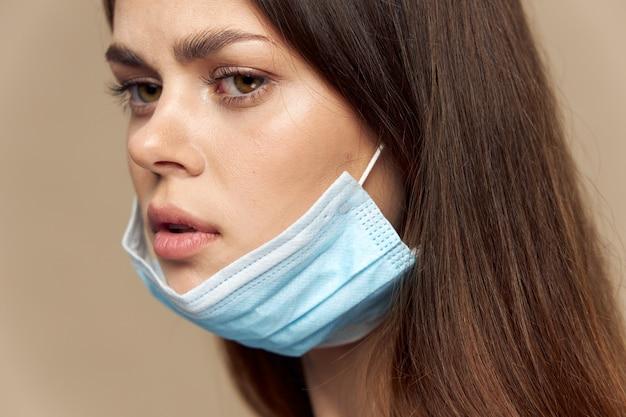 Schönes mädchen mit einer medizinischen maske auf ihrem gesicht schaut zur seite auf einer beige hintergrundbrünette