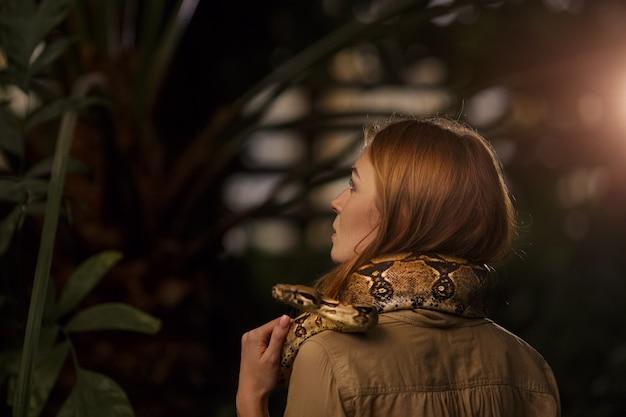 Schönes mädchen mit einer python auf den schultern. blick von hinten