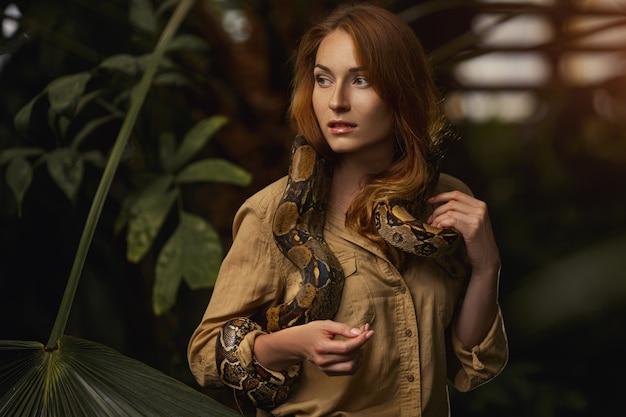 Schönes mädchen mit einer python auf den schultern