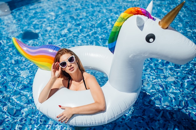 Schönes mädchen mit einer schönen abbildung steht still und nimmt in einem pool ein sonnenbad