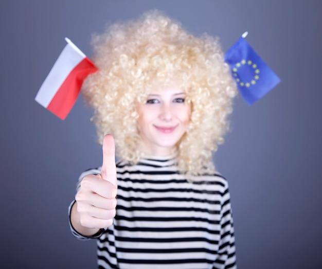 Schönes mädchen mit flagge der europäischen union und polens auf kopf zeigen ok.