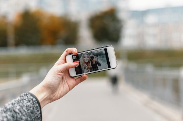 Schönes mädchen mit freund fotograf, um fotos am telefon zu machen