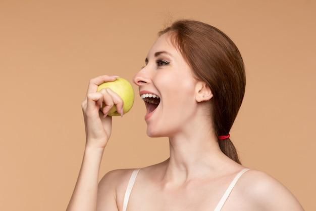 Schönes mädchen mit gebundenem auf hinterem haar geschmackvollen apfel essend.