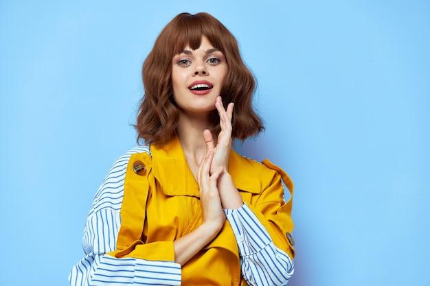 Schönes mädchen mit gelbem mantel, der ihre hände verbindet