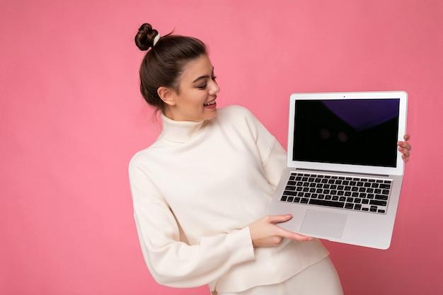 Schönes mädchen mit gesammelten brünetten haaren trägt weißen pullover mit computer-laptop computer