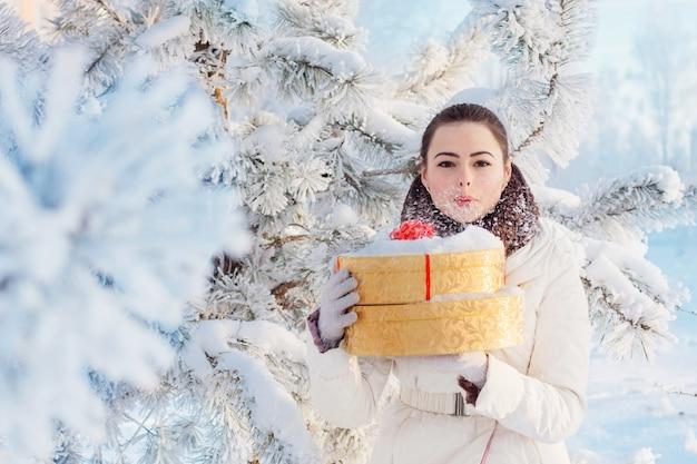 Schönes mädchen mit geschenk im winterpark