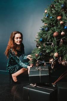 Schönes mädchen mit geschenkbox nahe weihnachtsbaum für plakat