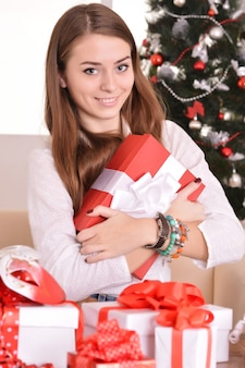 Schönes mädchen mit geschenken in der nähe des weihnachtsbaums