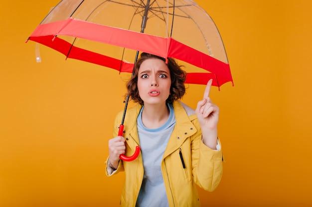 Schönes mädchen mit gewellter frisur, die lustige gesichter macht, während sie mit trendigem regenschirm aufwirft. foto der unglücklichen weißen frau im herbstmantel, der roten sonnenschirm hält.