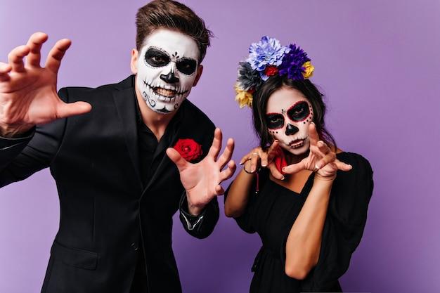 Schönes mädchen mit gruseligem make-up, das mit freund in halloween abkühlt. innenfoto des sorglosen paares, das spaß an der partei in vampirkostümen hat.