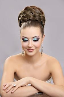 Schönes mädchen mit hellem make-up und hohem haar.