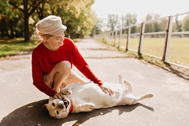 Schönes mädchen mit ihrem hund, der zusammen im park spielt. stilvolle blondine und ihr haustier, das sich im herbst unter der sonne entspannt.
