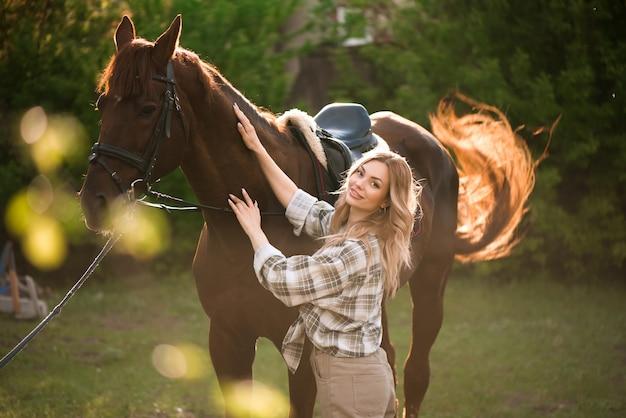 Schönes mädchen mit ihrem pferd und schönem warmen sonnenuntergang im frühlingswald.