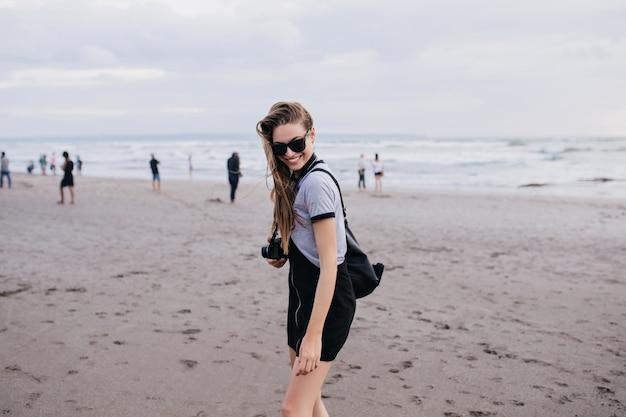 Schönes mädchen mit kamera, die zeit am sandstrand am bewölkten tag verbringt. foto im freien des angenehmen weiblichen fotografen, der während des wochenendes auf see lacht.