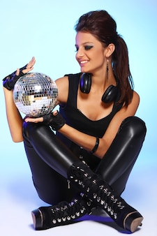 Schönes mädchen mit kopfhörern und discokugel
