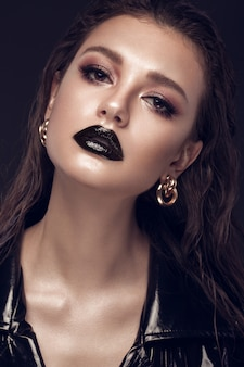 Schönes mädchen mit kreativem kunstmake-up, schwarzem kleid und goldzubehör. beauty gesicht.