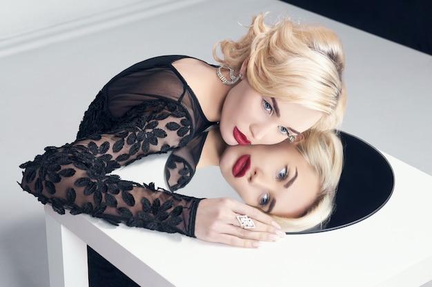 Schönes mädchen mit langen blonden lockigen haaren. perfektes frauenporträt auf dem tisch im spiegel. wunderschönes haar und schöne augen. natürliche schönheit, saubere haut, gesichtspflege und haare