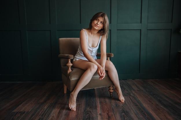 Schönes mädchen mit langen, dünnen beinen, das auf einem stuhl auf dunkelgrünem hintergrund sitzt sitting