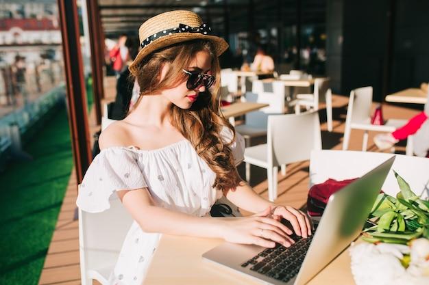 Schönes mädchen mit langen haaren im hut sitzt am tisch auf der terrasse im café. sie trägt ein weißes kleid mit nackten schultern, rotem lippenstift und sonnenbrille. sie tippt ernsthaft auf dem laptop.