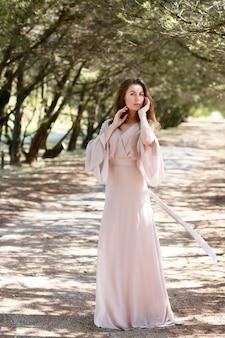 Schönes mädchen mit langen haaren in einem hellen kleid, das auf den wäldern steht